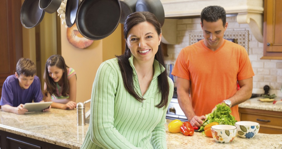 Happy Woman With Family In Kitchen